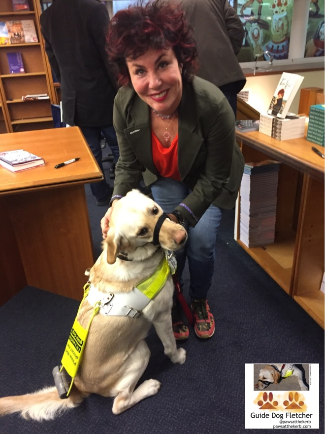 Me guide dog Fletcher sitting down receiving fuss from Ruby Wax