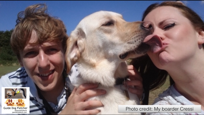 Me guide dog Fletcher giving one of my boarders a sloppy kiss. You see the heads of all three of us. To the left is one boarder, a youngish white male with brown hair. I'm in the middle. To the right is my boarder, a youngish white female with darker brown long hair. We're in the sun and the sky is bright blue. @pawsatthekerb
