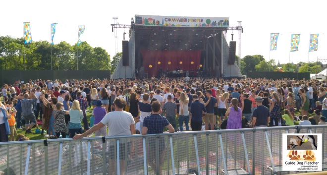 My view of the Common People stage. The stage is rectangular and in the distance surrounded by flags and green trees. Most of the photo are people of different ages standing with their backs to the camera in the sunshine. @pawsatthekerb