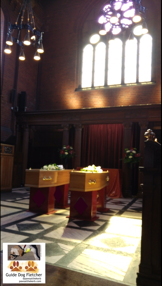 Two raised wooden coffins side by side with roses on top. The rays of the sun are catching the coffins and the stain glass window behind them.